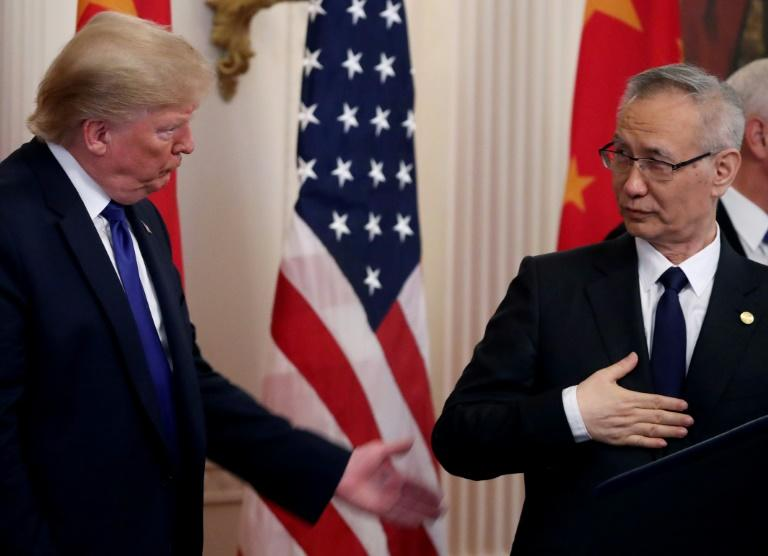 President Donald Trump stands with Chinese Vice PremierLiuHe, before signing a preliminary trade deal between the US and China (AFP Photo/MARK WILSON)