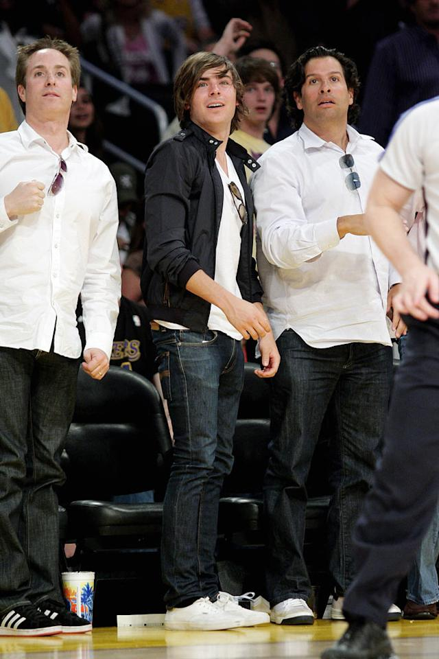"Zac Efron cheers on the Lakers from his seat in a section apparently reserved for men wearing jeans, white shirts, and sunglasses hanging from their neckline. Noel Vasquez/<a href=""http://www.gettyimages.com/"" target=""new"">GettyImages.com</a> - May 27, 2009"