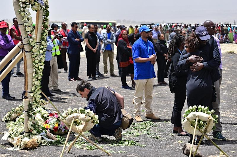 Colleagues of victims of the UN's World Food Programme office in Addis Ababa hugged in grief as they visited the crash site. The UN lost 22 staffers on the flight (AFP Photo/TONY KARUMBA)