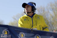 FILE — In this April 17, 2017, file photo, Race Director Dave McGillivray looks on from the platform at the start of the 2017 Boston Marathon in Hopkinton, Mass. Event organizers and other unconventional logistics experts are using their skills to help the nation vaccinate as many people against COVID-19 as possible. Since the 2021 Boston Marathon is on hold until fall, McGillivray has been tapped by the state of Massachusetts to run mass vaccination operations at Gillette Stadium and Fenway Park. (AP Photo/Mary Schwalm, File)