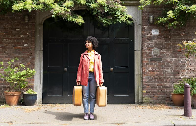 A young woman with suitcases in the city.