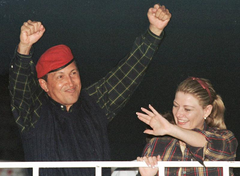 FILE - In this Dec. 2, 1998 file photo, presidential candidate Hugo Chavez and his wife Marisabel wave to supporters during his closing campaign rally in Caracas, Venezuela. After four election wins, his latest in Oct. 2012, Chavez is on track to completing at least 20 years in power. (AP Photo/Timothy Padek, File)