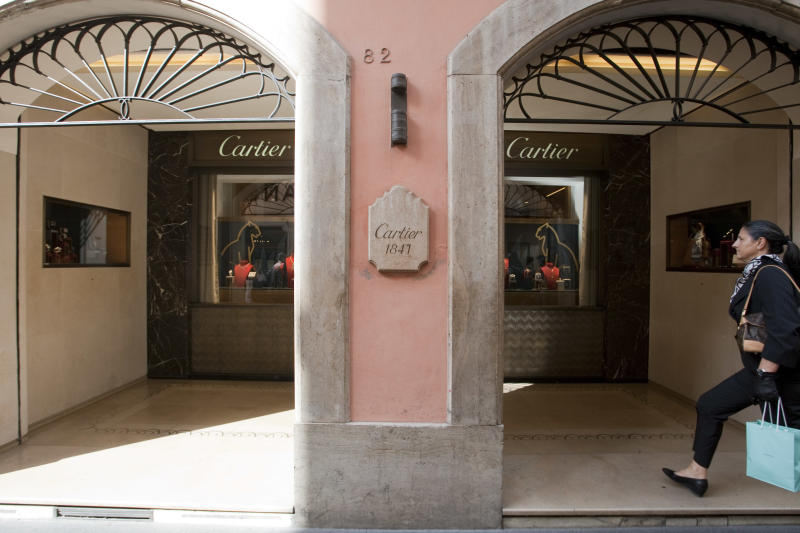 A woman walks past a Cartier jewelry shop in Rome's via Condotti, Wednesday, Oct. 20, 2010. Rome police are describing the thieves who calmly walked off with a €500,000 ($692,000) diamond-encrusted ring as a pair of elegantly attired, smooth-talking bilingual men who convinced a Cartier saleswoman they wanted the luxury store's most expensive ring as a wedding present. Police official Paolo Guiso, who is leading the investigation, told The Associated Press Wednesday that two men, speaking Arabic and French, talked their way into seeing several pieces in the store on Via Condotti, a posh shopping street. (AP Photo/Andrew Medichini)