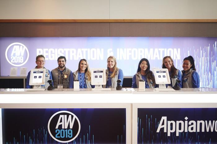 Seven people behind a desk marked Appianworld 2019.