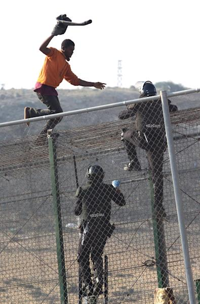 A sub-Saharan migrant tries to escape from Spanish Guardia Civil officers, on top of a metallic fence that divides Morocco and the Spanish enclave of Melilla, Thursday, May 1, 2014. Spain says around 700 African migrants have rushed its barbed wire border fences in the North African enclave of Melilla, and although police repelled most, 140 managed to enter Spanish territory. The migrants charged the fences in two waves, with 500 arriving in the early hours and another 200 later Thursday morning. Spain and Morocco stepped up border vigilance in Feb. when 15 migrants drowned trying to enter Spain's other north African coastal enclave, Ceuta. (AP Photo/Fernando Garcia)