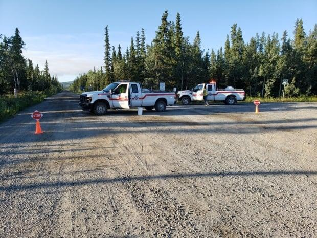 Fire crews block Aishihik Road east of Haines Junction, Yukon, on Saturday. Wildland Fire Management says the road will be closed until at least Monday because of a wildfire. (Wally Bootsma - image credit)