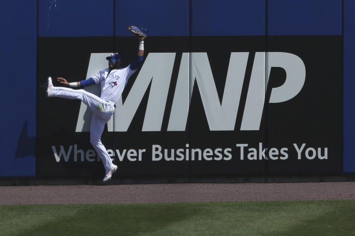 Toronto Blue Jays left fielder Lourdes Gurriel Jr. (13) makes a leaping catch to get out Houston Astros' Alex Bregman during the sixth inning of a baseball game in Buffalo, N.Y., Sunday, June 6, 2021. (AP Photo/Joshua Bessex)