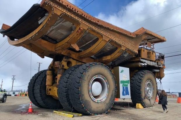 Tanea Hynes is overshadowed by one of the huge trucks used at the Iron Ore Co. of Canada mine in Labrador City. She revisited the town where she grew up in a new exhibit called Workhorse.  (Darryl Dinn/CBC - image credit)