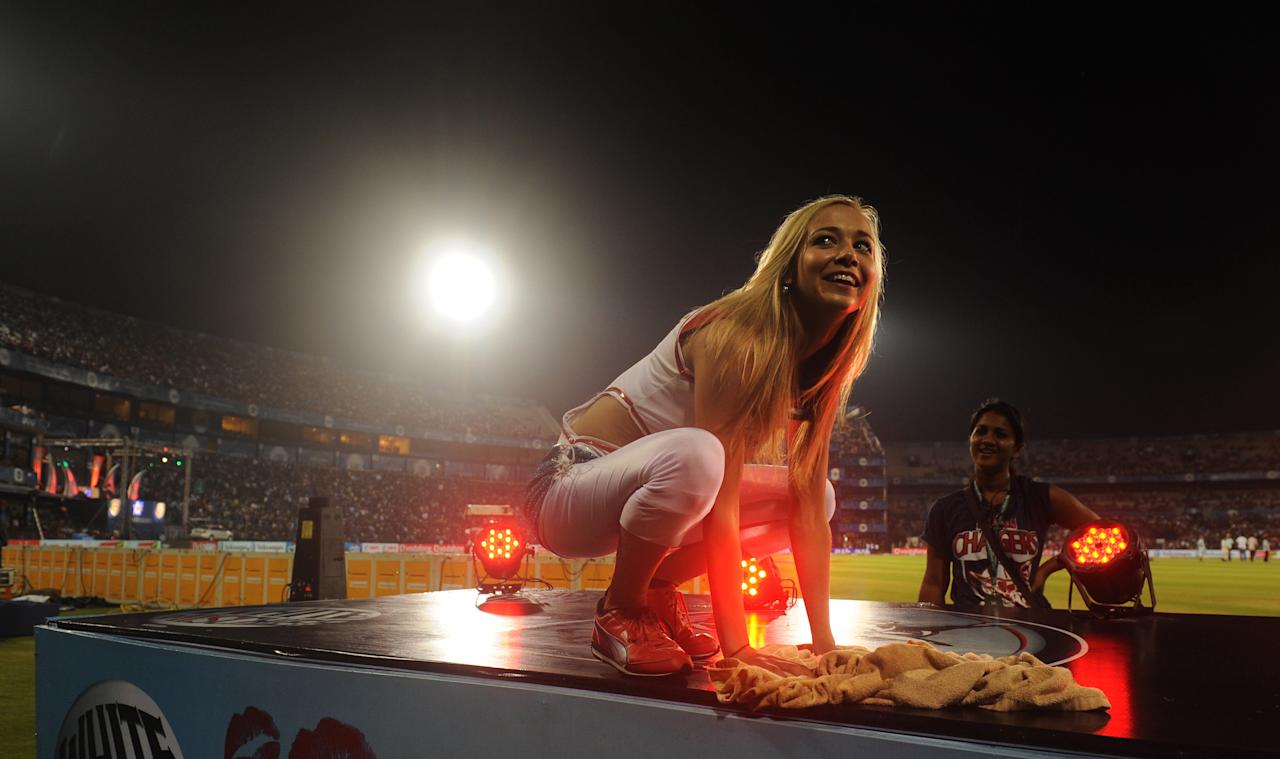 A Deccan Chargers cheerleader clears water off their platform as the IPL Twenty20 cricket match between Deccan Chargers and Kolkata Knight Riders is delayed due to rain at The Barabati Stadium in Cuttack on April 22, 2012.  RESTRICTED TO EDITORIAL USE. MOBILE USE WITHIN NEWS PACKAGE.    AFP PHOTO/Dibyangshu SARKAR (Photo credit should read DIBYANGSHU SARKAR/AFP/Getty Images)