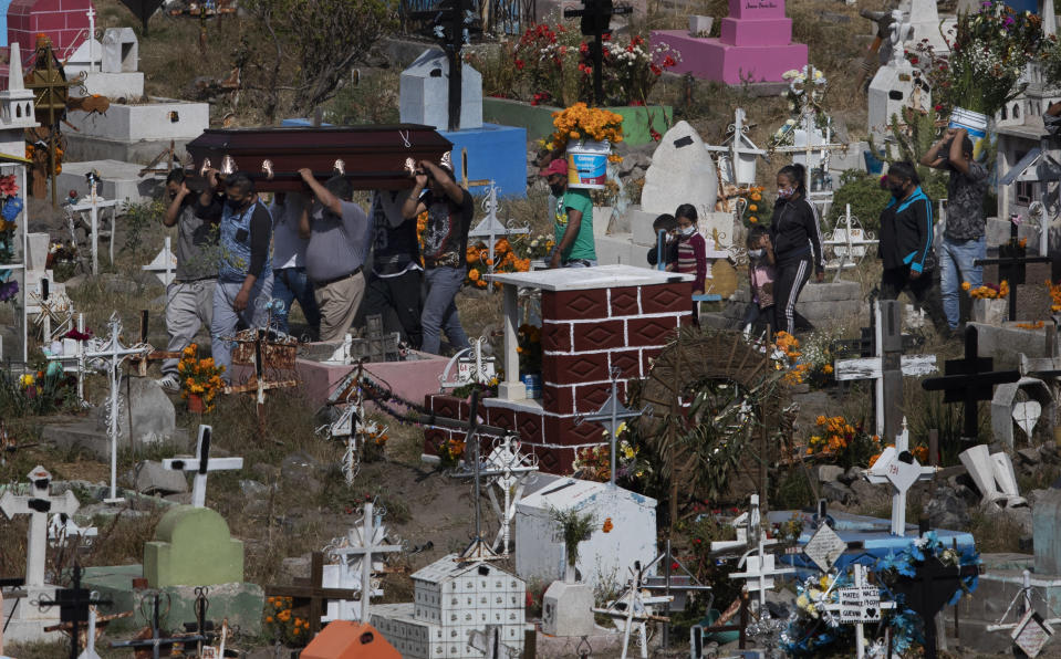 People carry the coffin that contains the remains of a relative at the Valle de Chalco Municipal Cemetery on the outskirts of Mexico City, Saturday, Oct. 31, 2020. Mexico's Day of the Dead celebration this weekend won't be the same in a year so marked by death after more than 90,000 people have died of COVID-19. (AP Photo/Marco Ugarte)