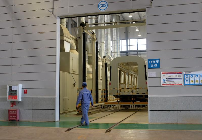 A CRRC worker walks past an unfinished metro train car in the company's Kunming factory