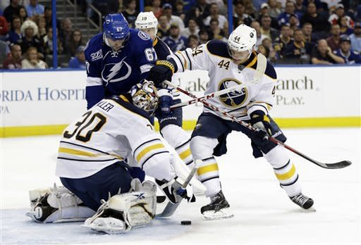 Buffalo Sabres goalie Ryan Miller (30) dives on a shot by Tampa Bay Lightning left wing Benoit Pouliot (67) during the second period of an NHL hockey game Tuesday, Feb. 26, 2013, in Tampa, Fla. Defending for the Sabres is Andrej Sekera (44), of Slovakia. (AP Photo/Chris O'Meara)