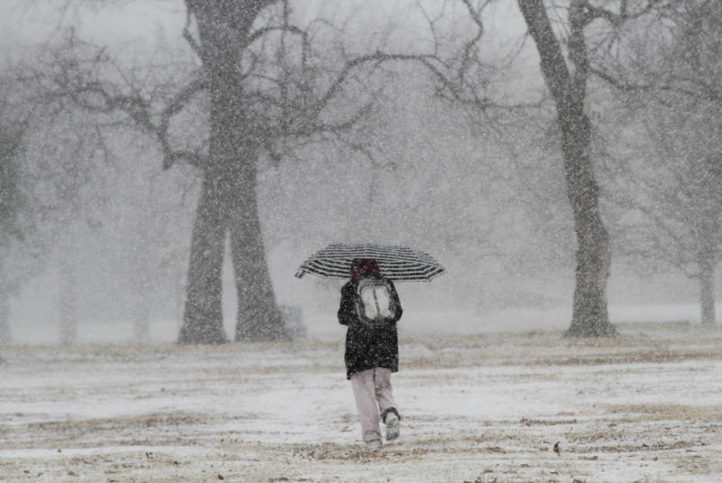 A woman walks through Central Riverside Park on a snowy Wednesday morning in Wichita, Kan., Feb. 20, 2013. Hundreds of snow plows and salt spreaders took to the highways of the nation's heartland Wednesday, preparing for a winter storm that could dump up to a foot of snow in some regions and bring dangerous freezing rain and sleet to others. (AP Photo/The Wichita Eagle, Jaime Green)
