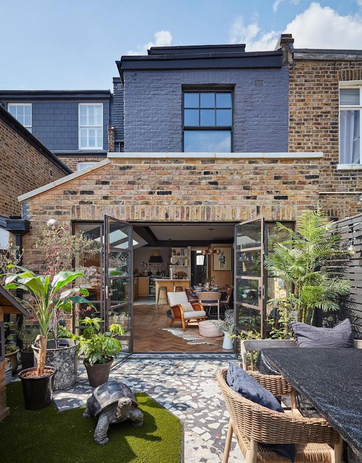 """AFTER: The extended family room opens up to a spacious garden at the back of the house, which is covered with fast-drying Astroturf and terrazzo tiles. """"These glazed doors forced us to rush the garden design, because it obviously had to look good from day one,"""" says Anna."""