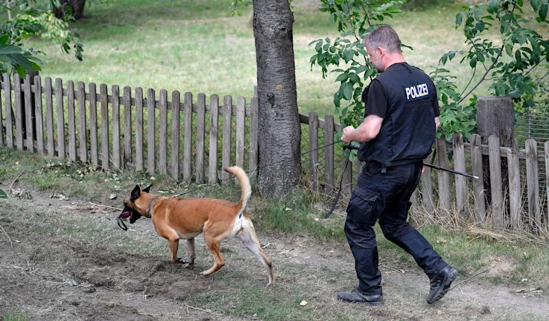 Germany police officers search with dogs an allotment garden plot in Seelze (AP)