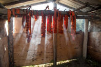 In this undated photo provided by the Tanana Chiefs Conference, salmon hangs on a drying rack at a fish camp in Fort Yukon, Alaska. Families traditionally spend the summer at fish camps using nets and fish wheels to snag adult salmon as they migrate inland from the ocean to the place where they hatched so they can spawn. The salmon is prepared for storage a variety of ways: dried for jerky, cut into fillets that are frozen, canned in half-pint jars or preserved in wooden barrels with salt. (Rachel Saylor/Tanana Chiefs Conference via AP)
