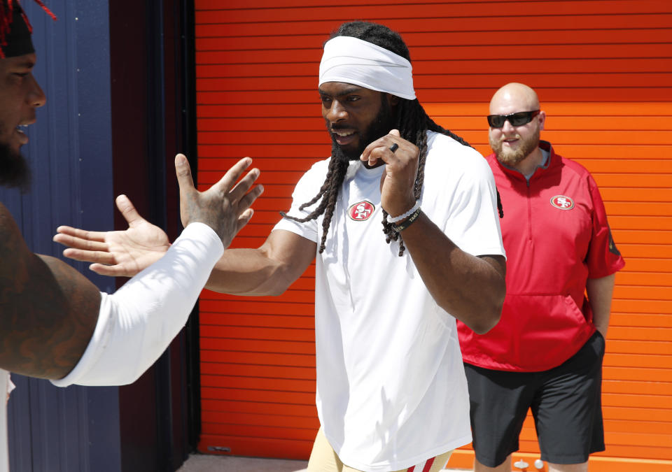 San Francisco 49ers cornerback Richard Sherman, right, greets middle linebacker Kwon Alexander as he heads up to the podium to speak to reporters after a combined NFL football training camp with the Denver Broncos at the Broncos' headquarters Friday, Aug. 16, 2019, in Englewood, Colo. (AP Photo/David Zalubowski)