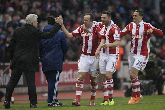 Stoke's Charlie Adam, centre, celebrates with teammates and manager Mark Hughes, left, after scoring his second goal against Manchester United during their English Premier League soccer match at the Britannia Stadium, Stoke, England, Saturday Feb. 1, 2014. (AP Photo/Jon Super)