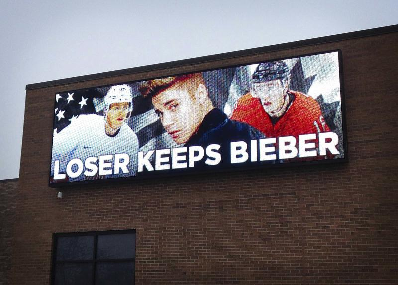 An electronic billboard sign shows an image of pop star Justin Bieber sandwiched between U.S. and Canadian hockey players on a wall in Skokie, Illinois February 20, 2014. Hockey titans Canada and the United States played their men's ice hockey semi-final game at the Sochi 2014 Winter Olympic Games on Friday. Picture taken February 20, 2014. REUTERS/Commandtransportation.com via Reuters (UNITED STATES - Tags: SPORT ICE HOCKEY OLYMPICS ENTERTAINMENT PROFILE) NO SALES. NO ARCHIVES. FOR EDITORIAL USE ONLY. NOT FOR SALE FOR MARKETING OR ADVERTISING CAMPAIGNS. THIS IMAGE HAS BEEN SUPPLIED BY A THIRD PARTY. IT IS DISTRIBUTED, EXACTLY AS RECEIVED BY REUTERS, AS A SERVICE TO CLIENTS