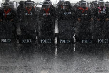 Heavy rain falls on policemen taking positions as rubber farmers protest near the airport in Surat Thani