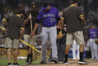 Colorado Rockies relief pitcher Carlos Estevez (54) talks with the San Diego Padres grounds crew as they fix the mound during the seventh inning of a baseball game Saturday, July 31, 2021, in San Diego. (AP Photo/Derrick Tuskan)