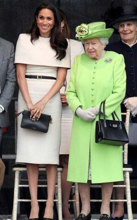 The Duchess wore a knee-length Givenchy dress with a shoulder cuff and black clutch, while the Queen dressed in a green outfit for Grenfell - Credit: PA
