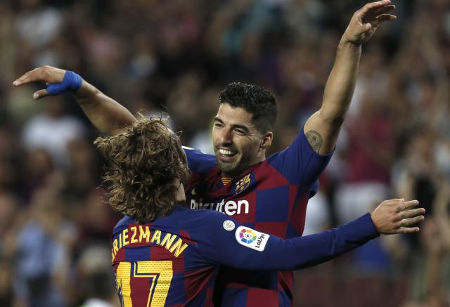 Barcelona's Luis Suarez, right, celebrates with teammate Antoine Griezmann after scoring his side's fifth goal during the Spanish La Liga soccer match between FC Barcelona and Valencia CF at the Camp Nou stadium in Barcelona, Spain, Saturday, Sep. 14, 2019. (AP Photo/Joan Monfort)