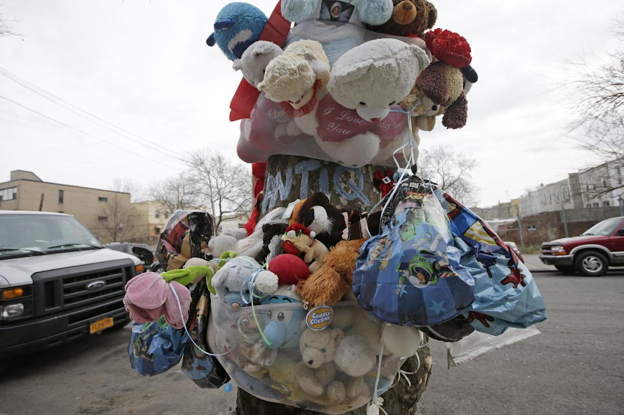 Children's stuffed animals and balloons make up a memorial for slain one-year-old Antiq Hennis in front of his mother's apartment, Monday, Dec. 30, 2013, in the Brownsville section of New York. Hennis was fatally shot Sept. 1 by a stray bullet while being wheeled across the street in his stroller. Police believe the boy's father was the intended target of the shooting, but the father refused to cooperate in identifying the shooter. Year-end boasts by Mayor Michael Bloomberg that New York is the safest big city in America ring hollow in Brownsville, a neighborhood of entrenched gang violence that has proven stubbornly immune to strategies that have pushed crime to historic lows across the rest of the city. (AP Photo/Kathy Willens)