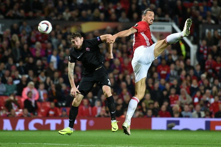 Manchester United's striker Zlatan Ibrahimovic (R) vies in the air with Zorya's Belarusian defender Mikhail Sivakov as he heads the ball towards goal during the UEFA Europa League group A football match between Manchester United and Zorya Luhansk