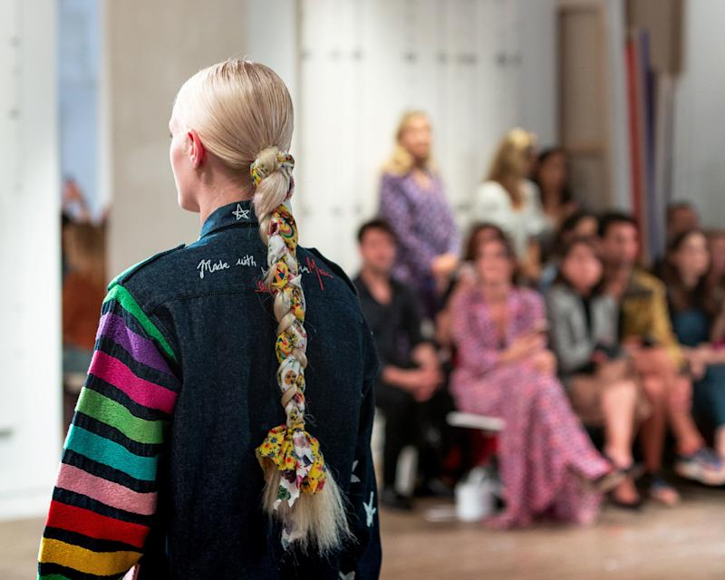 A model's decorated blonde ponytail (created by hairstylist Laurent Philippon) plays off the striped top embroidered by Mexican artisans; on the front are white stars, in homage to the American flag.
