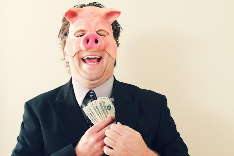a businessman with a pig mask on holding cash money.