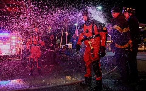 A rescue diver is hosed off with fresh water after pulling victims from the submerged helicopter - Credit: Darren Ornitz/Reuters