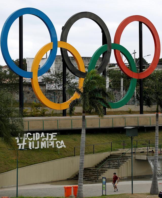 A man walks near Olympic rings placed at Madureira Park ahead of the Rio 2016 Olympic Games in Rio de Janeiro, Brazil, July 17, 2016. REUTERS/Bruno Kelly