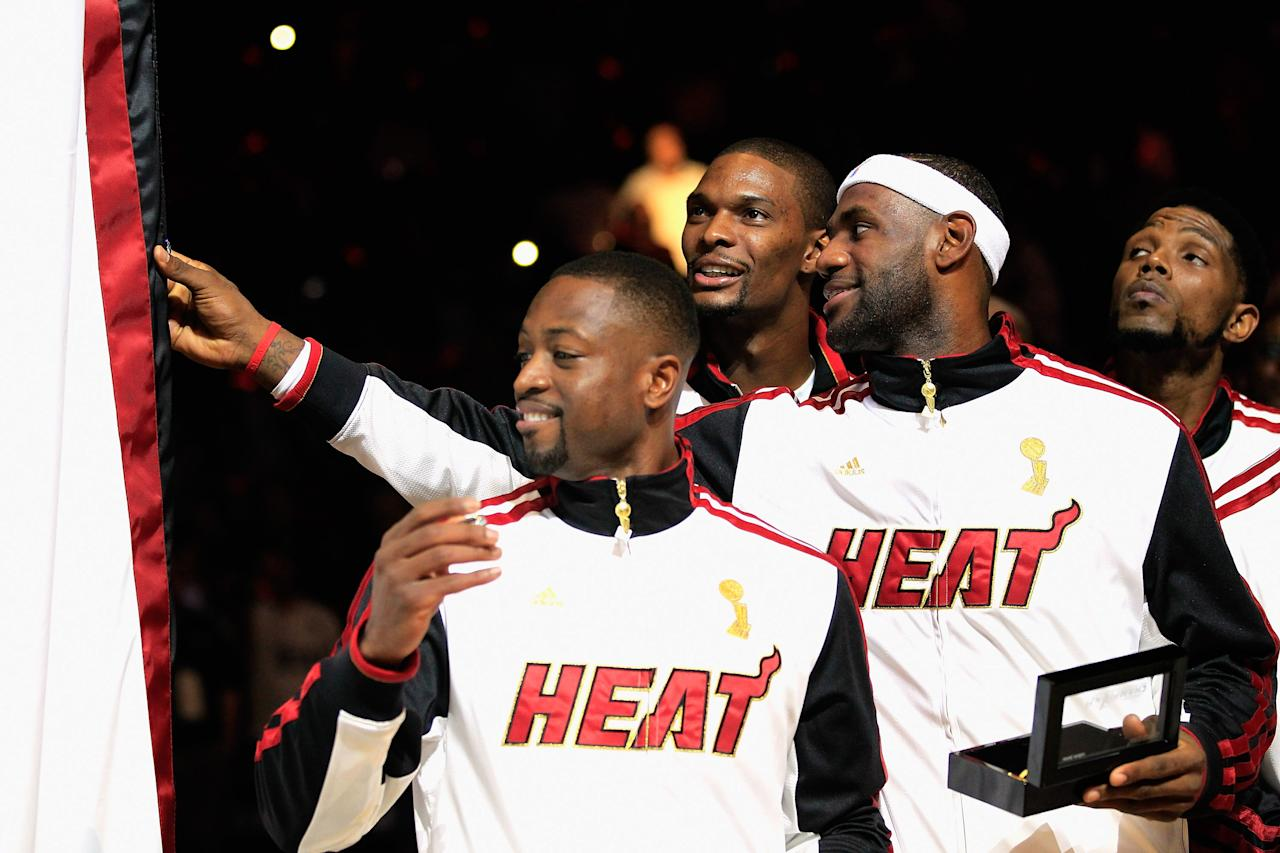 MIAMI, FL - OCTOBER 30:  (L) Dwyane Wade #3 of the Miami Heat, (C) Chris Bosh #1 of the Miami Heat and (R) LeBron James #6 of the Miami Heat look at the 2012 NBA Championship banner following the ring ceremony prior to the game against the Boston Celtics at American Airlines Arena on October 30, 2012 in Miami, Florida. NOTE TO USER: User expressly acknowledges and agrees that, by downloading and/or using this Photograph, user is consenting to the terms and conditions of the Getty Images License Agreement.  (Photo by Chris Trotman/Getty Images)