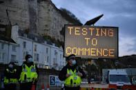 A sign in the English port of Dover says Covid-19 testing is set to begin on truck drivers who have been queueing to leave the UK