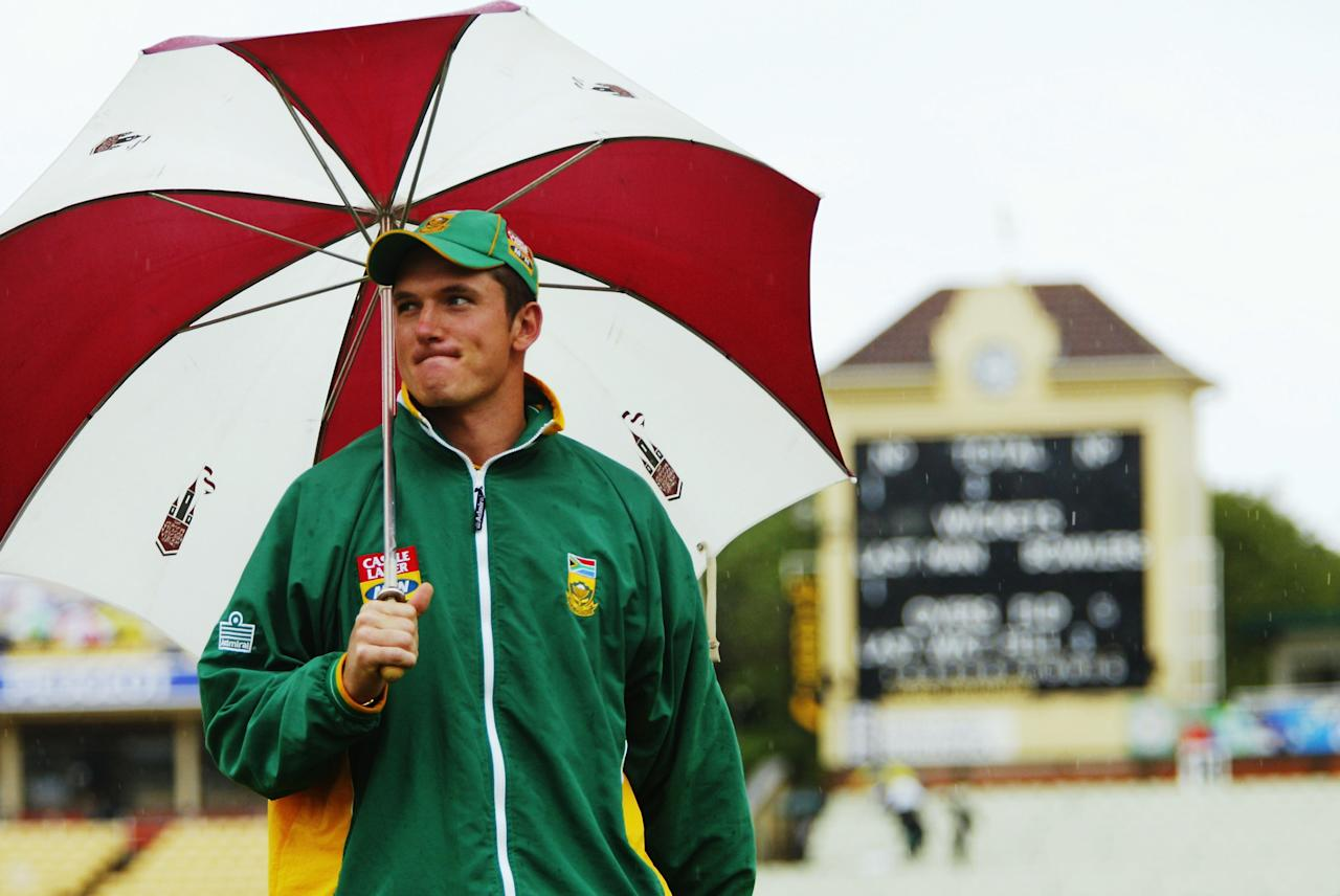 BIRMINGHAM - JULY 25:  Graeme Smith of South Africa takes shelter from the rain during the second day of the first npower test match between England and South Africa held on July 25, 2003 at the Edgbaston Cricket Ground, in Birmingham, England. (Photo by Tom Shaw/Getty Images)