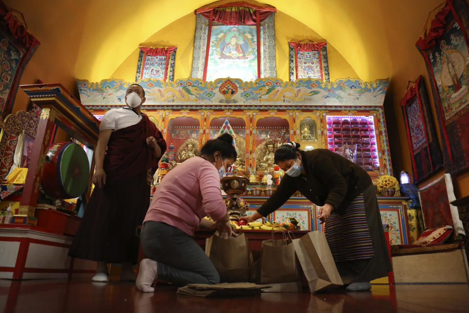 Lama Gelbu, left, Pasang Sherpa, center, and Yanddu Lama, right, prepare bags of fruit used as ceremonial offerings at the conclusion of the Dakini Day practice, a group meditation that includes song and food and is celebrated on the 25th day of each lunar month, at the United Sherpa Association in the Queens borough of New York on Friday, Jan. 8, 2021. (AP Photo/Jessie Wardarski)