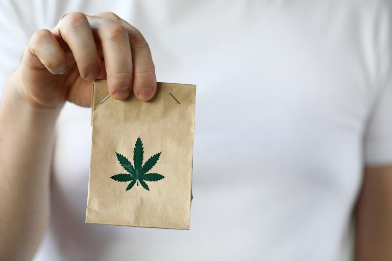 Courier hand passing package with marijuana to client close-up