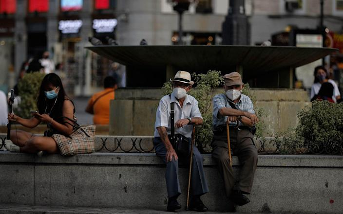 Residents of Madrid wear face masks as they sit by a fountain in the Spanish capital on Wednesday - Anadolu
