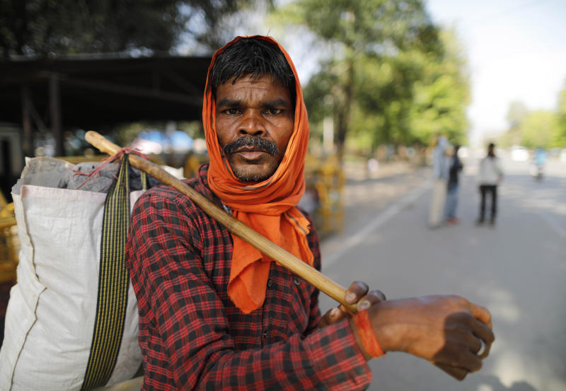 Hiralal, a daily wage laborer, leaves for his village as the city comes under lockdown in Prayagraj, India , Thursday, March 26, 2020. Some of India's legions of poor and people suddenly thrown out of work by a nationwide stay-at-home order began receiving aid distribution Thursday, as both the public and private sector work to blunt the impact of efforts to curb the coronavirus pandemic. Untold numbers of them are now out of work and many families have been left struggling to eat. (AP Photo/Rajesh Kumar Singh)