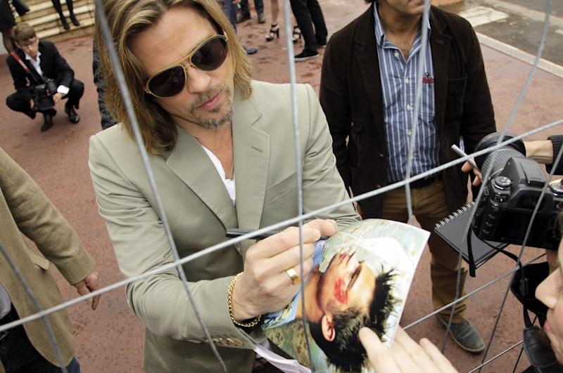 Actor Brad Pitt signs autographs as he arrives at a photo call for Killing Them Softly at the 65th international film festival, in Cannes, southern France, Tuesday, May 22, 2012. (AP Photo/Francois Mori)