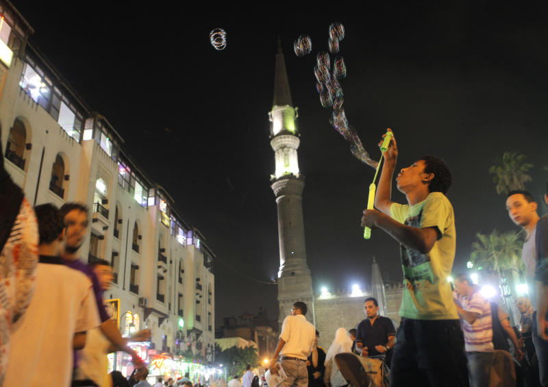 An Egyptian toys vendor blows bubbles to attract customers in front of Al-Hussein mosque in Cairo, Egypt, late, Monday, July 30, 2012.  (AP Photo/Amr Nabil)