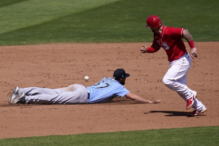 Cincinnati Reds' Tucker Barnhart, right, watches a single hit by Reds' Mark Payton get past Seattle Mariners third baseman Jantzen Witte (67) during the fifth inning of a spring training baseball game Monday, March 29, 2021, in Goodyear, Ariz. (AP Photo/Ross D. Franklin)