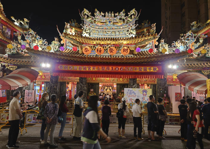 People wear face masks to protect against the spread of the coronavirus and line up to enter a temple in Taipei, Taiwan, Friday, April 30, 2021. (AP Photo/Chiang Ying-ying)