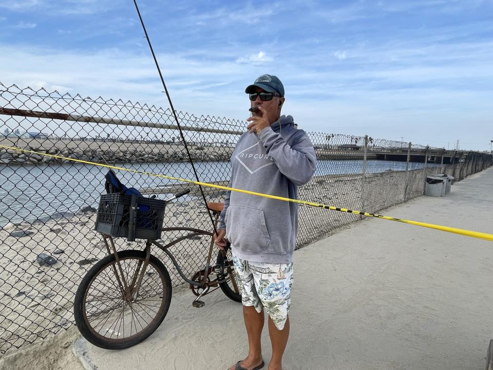 Huntington Beach resident Alex Bauer enjoys a cigar as he watches the waves where he would normally be fishing. (Garin Flowers/Yahoo News)