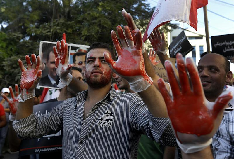 Lebanese pro-Syrian regime supporters, with their hands painted in red to symbolize blood, attend a demonstration against a possible military strike in Syria, near the U.S. Embassy in Awkar, east of Beirut, Lebanon, Friday, Sept. 6, 2013. The prospect of a U.S.-led strike against Syria has raised concerns of potential retaliation from the Assad regime or its allies. The State Department ordered nonessential U.S. diplomats to leave Lebanon over security concerns and urged private American citizens to depart as well. (AP Photo/Hussein Malla)