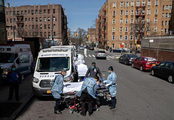 PHOTO: Medics and hospital workers prepare to lift a patient onto a hospital stretcher outside the Montefiore Medical Center Moses Campus, on April 7, 2020, in the Bronx borough of New York City. (John Moore/Getty Images)