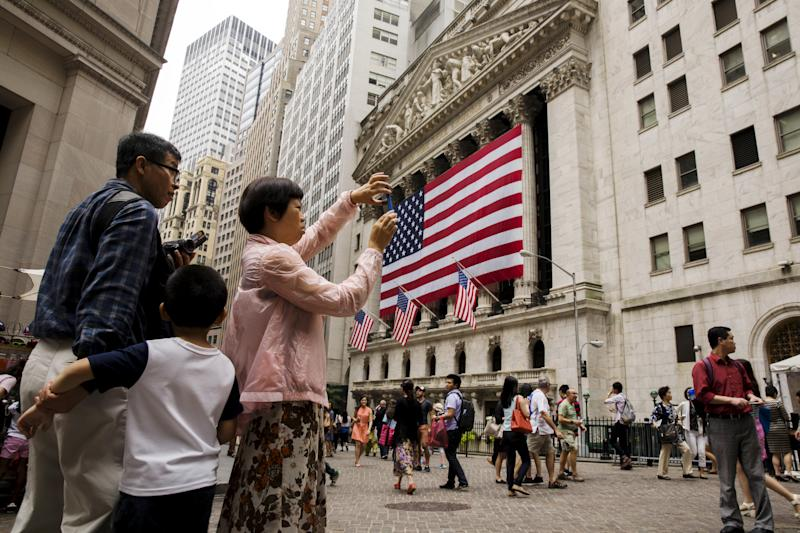 Chinese tourists take photographs outside of the New York Stock Exchange shortly after the opening bell in New York, July 8, 2015. REUTERS/Lucas Jackson