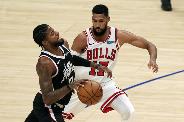 Los Angeles Clippers guard Paul George, left, dribbles next to Chicago Bulls guard Garrett Temple (17) during the first half of an NBA basketball game Sunday, Jan. 10, 2021, in Los Angeles. (AP Photo/Marcio Jose Sanchez)