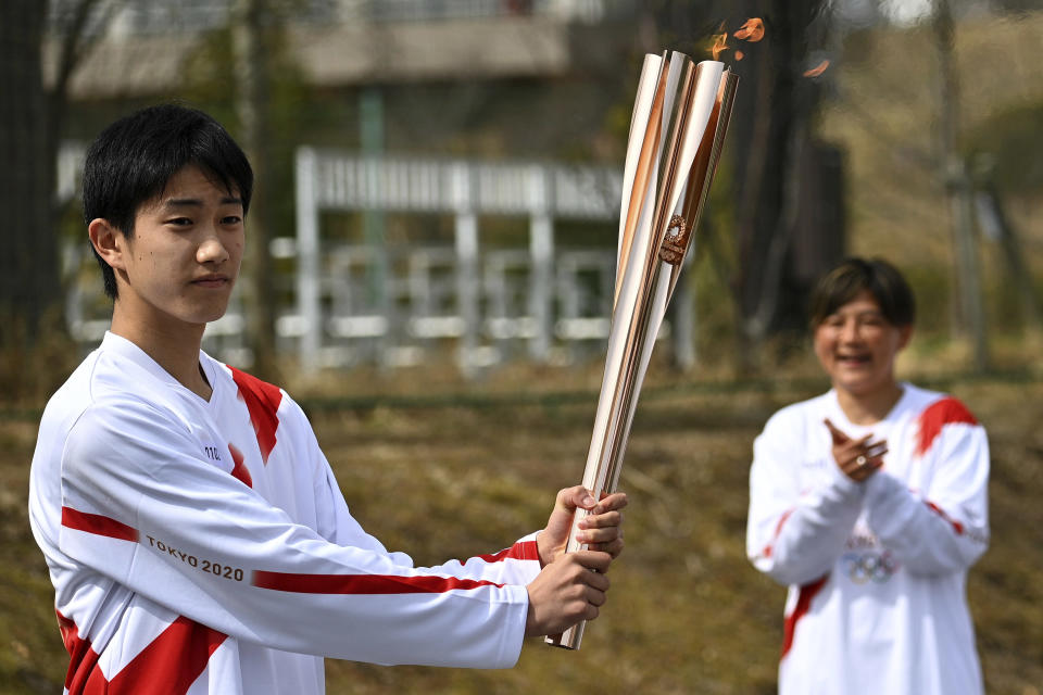 Japanese high school student Asato Owada holds an Olympic Torch after receiving the flame during the torch relay grand start outside J-Village National Training Center in Naraha, Fukushima prefecture, northeastern Japan, Thursday, March 25, 2021. The torch relay for the postponed Tokyo Olympics began its 121-day journey across Japan on Thursday and is headed toward the opening ceremony in Tokyo on July 23. (Philip Fong/Pool Photo via AP)